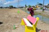 An employee of the City applies paint to one of several colourful benches at the park